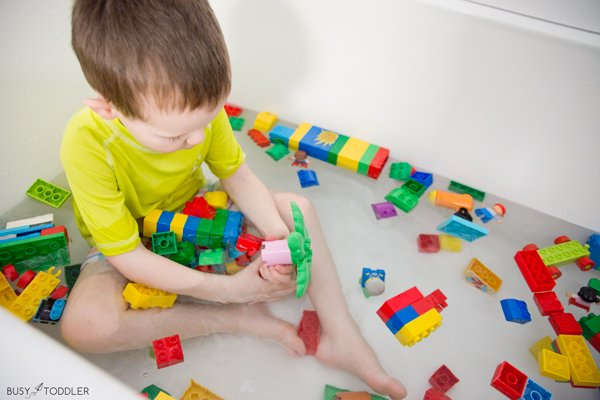 A toddler taking a bath with his LEGO duplos.