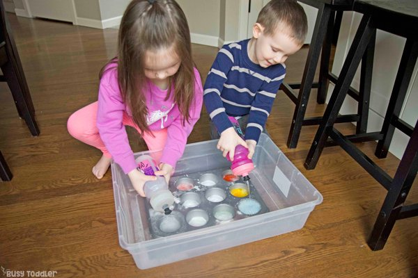 A science experiment activity with toddlers squeezing vinegar into a baking soda filled muffin tin.