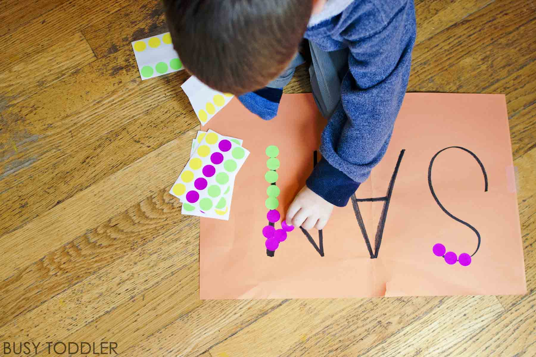 STICKER NAMES: A fine motor skills activity using stickers! An easy indoor toddler activity. Fun playing with letter names and name identification skills. A quick and easy activity.