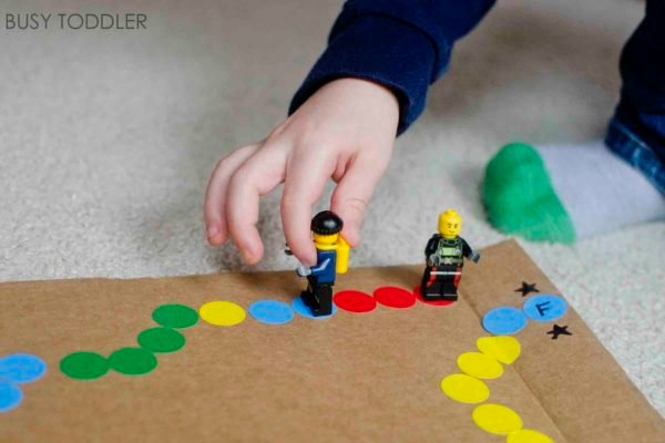 [Child's hand moving pieces in a home made board game.]