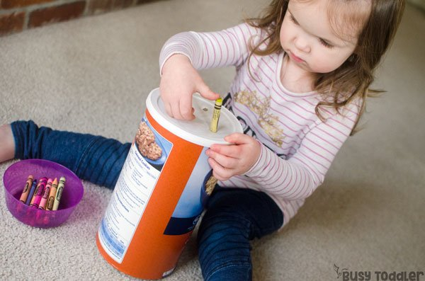 CRAYON PUSH: A quick and easy toddler activity that's so simple to make; a DIY toddler activity; a fun fine motor skills activity for toddlers; a rainy day activity for toddlers; easy activity for toddlers; quick activity, an easy DIY toddler toy - Busy Toddler