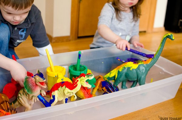 PAINTING DINOSAURS PROCESS ART: A silly easy toddler activity painting toy dinosaurs! Toddlers love this quick and easy activity that's perfect for a rainy day; an easy art activity; an easy toddler activity from Busy Toddler