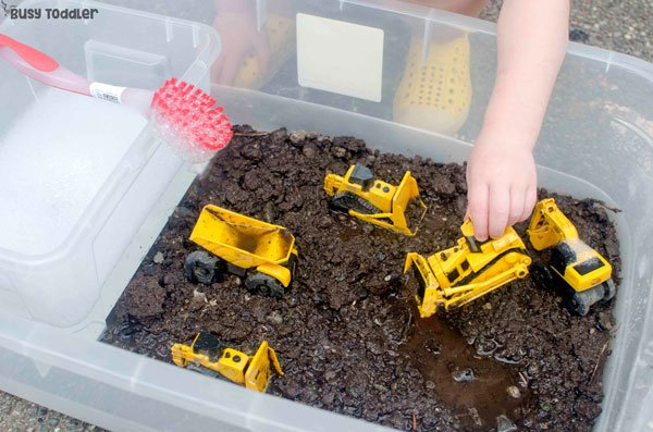 CLEAN THE TRUCKS SENSORY PLAY: A quick and easy toddler sensory bin that's perfect for outdoor fun. An easy outdoor activity for toddlers; a messy sensory activity that toddlers will love from Busy Toddler