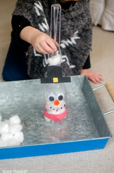 FEED THE SNOWMAN: A quick and easy toddler activity; winter toddler activity; a fun indoor toddler activity; an easy way to entertain a toddler; fine motor skills activity for toddlers from Busy Toddler