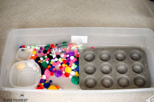 POM POM SENSORY BIN: A quick and easy indoor activity; an easy toddler activity; an easy sensory bin activity; pom pom ball activity; easy preschool activity from Busy Toddler