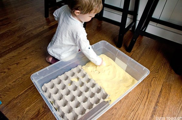 CORNMEAL SCOOPING STATION: An easy toddler activity; a quick taby activity; introducing sensory bins; life skills activity; easy indoor activity from Busy Toddler