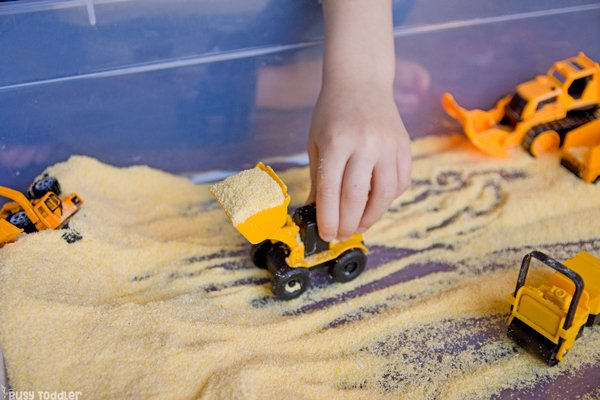 CORNMEAL CONSTRUCTION SITE - Check out this awesome sensory bin; an easy indoor activity; easy construction activity; sensory bin; toddler activity; preschool activity; construction themed sensory bin from Busy Toddler