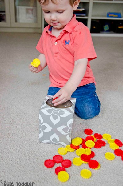 EASY DROP BOX ACTIVITY: Looking for an easy way to entertain a taby? Check out this drop box activity! A perfect way to play with a taby; taby activity; one-year-old activity; easy indoor activity; fine motor skills from Busy Toddler