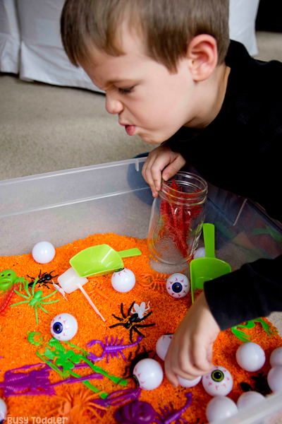 HALLOWEEN SENSORY ACTIVITY: A quick and easy Halloween sensory bin; dollar store sensory bin; cheap sensory activity; orange rice; Halloween activity for toddlers; Halloween activities for preschoolers from Busy Toddler