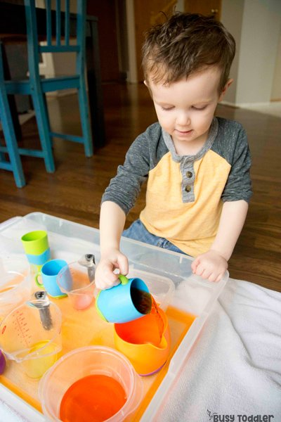 POURING SKILLS: How do you introduce pouring skills to toddlers? A quick and easy toddler sensory bin activity; a life skills activity for toddlers; pouring station activity; easy indoor activity; montessori activity from Busy Toddler