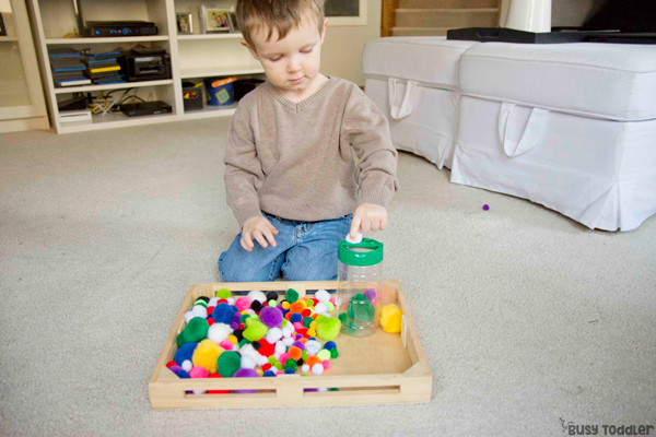 POM POM PUSHING: A quick and easy toddler activity; an indoor activity for toddlers; fine motor skill activity; easy pom pom activity; DIY toy; taby activity from Busy Toddler