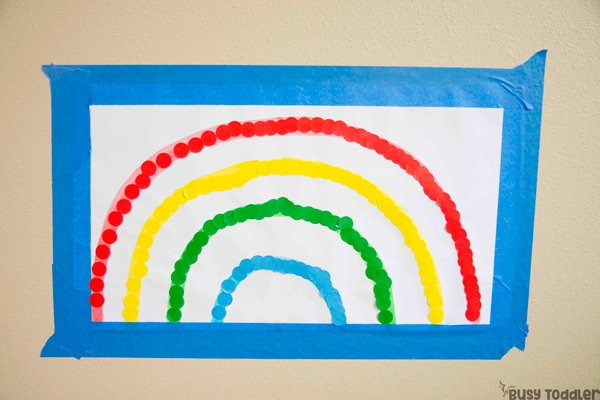 RAINBOW DOT STICKER LINE-UP: Check out this quick and easy toddler activity; an easy dot sticker activity; indoor activity; preschool activity; matching colors rainbow activity; fine motor skills activity; busy toddler activity; easy activity from Busy Toddler
