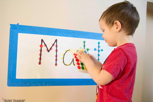 DOT STICKER NAME GAME: Learning how to use dot stickers? Try this quick and easy toddler activity! Letter recognition; name activity; spelling names; alphabet activity; dot sticker activity; fine motor activity from Busy Toddler