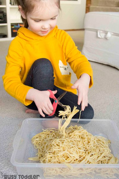 SPAGHETTI CUTTING BIN - Scissor practice; scissor skills for preschoolers; introducing scissors; fine motor skills; easy sensory activity for toddlers; taste safe sensory activity; indoor activity; quick and easy activity from Busy Toddler