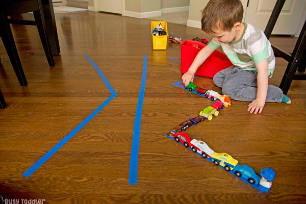 CAR PARADE: Make a quick and easy toddler activity by setting up a parade of cards; a great indoor activity for a rainy day; transportation themed activity; fun toddler play from Busy Toddler