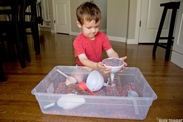RAINBOW RICE SENSORY BIN ACTIVITY: A toddler playing with rainbow rice in a quick and easy sensory bin activity from Busy Toddler using colored rice, funnels, and scoops for a simple life skills activity