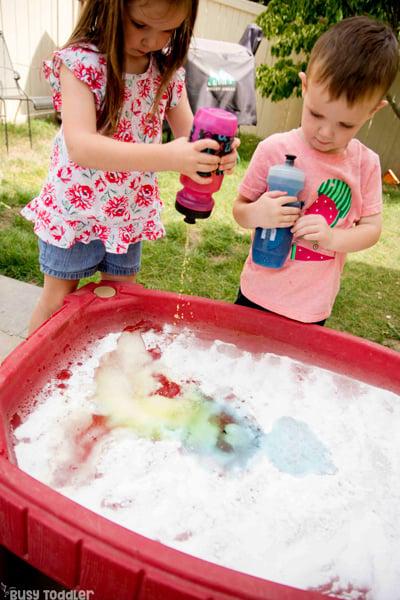 TABLA DE CIENCIAS: un niño en edad preescolar y un niño pequeño que juegan una actividad científica rápida y fácil en su mesa de arena usando bicarbonato de sodio y vinagre para una actividad de experimento científico fuera de Busy Toddler