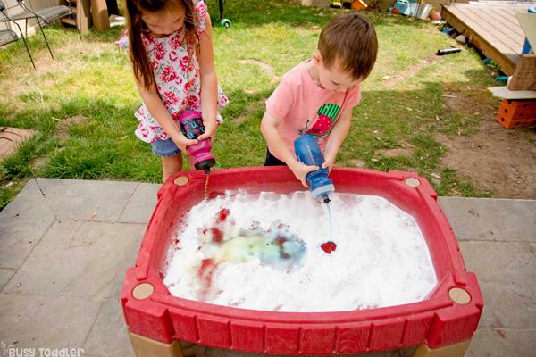 TABLA DE CIENCIAS: Un niño en edad preescolar y un niño pequeño que juegan una actividad científica rápida y fácil en su mesa de arena usando bicarbonato de sodio y vinagre para una actividad de experimento científico realizada fuera de Busy Toddler
