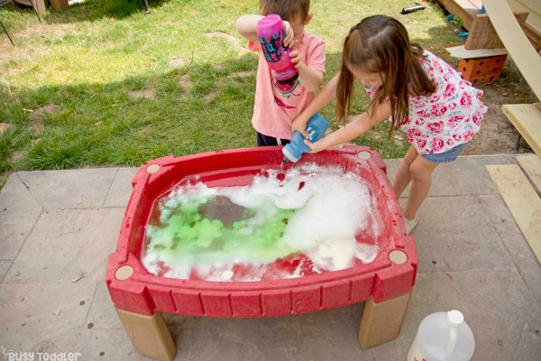 SCIENCE TABLE:  A preschooler and a toddler playing a quick and easy science activity at their sand table using baking soda and vinegar for a science experiment activity done outside from Busy Toddler