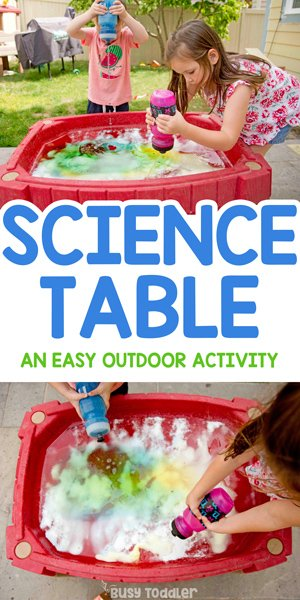 TABLA DE CIENCIAS: Un niño en edad preescolar y un niño pequeño jugando una actividad científica rápida y fácil en su mesa de arena usando bicarbonato de sodio y vinagre para una actividad de experimento científico realizada fuera de Busy Toddler