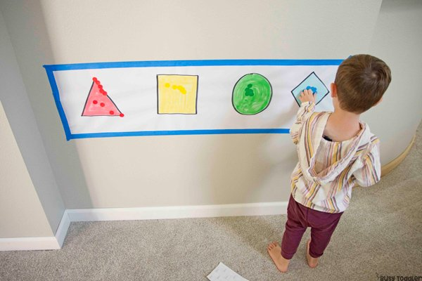 STICKER SHAPES ACTIVITY FOR TODDLERS: A toddler playing with a quick and easy dot sticker activity from Busy Toddler. Working on sorting colors and shape identification in an easy math activity.