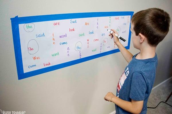 Kindergarten trabajando en una actividad de palabras de vista para ayudar a memorizar palabras difíciles en una actividad simple de Busy Toddler