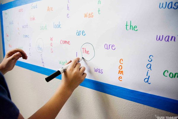Kindergarten trabajando en una actividad de palabras a la vista para ayudar a memorizar palabras difíciles en una actividad simple de Busy Toddler