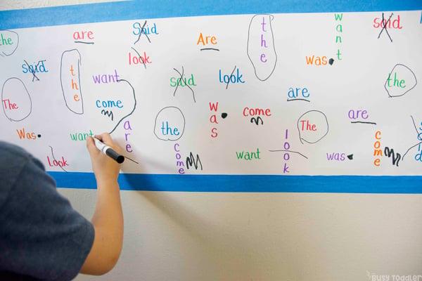 Kindergartener trabajando en una actividad de palabras visuales para ayudar a memorizar palabras difíciles en una actividad simple de Busy Toddler