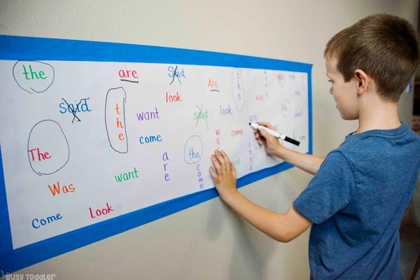 Kindergartener que trabaja en una actividad de palabras a la vista para ayudar a memorizar palabras difíciles en una actividad simple de Busy Toddler