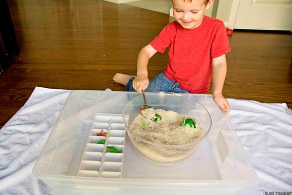 Un niño pequeño que realiza una actividad sensorial del compartimiento rescatando dinosaurios de una trampa de arroz en una actividad rápida y fácil de Busy Toddler