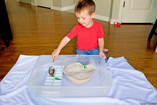 Un niño pequeño que realiza una actividad sensorial en el compartimiento rescatando dinosaurios de una trampa de arroz en una actividad rápida y fácil de Busy Toddler