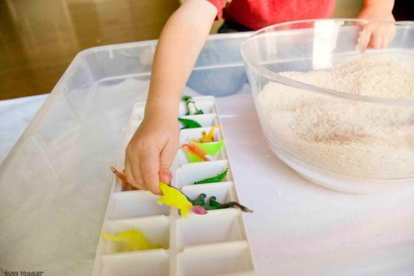 Un niño pequeño que realiza una actividad sensorial de contenedores que rescata a los dinosaurios de una trampa de arroz en una actividad rápida y fácil de Busy Toddler
