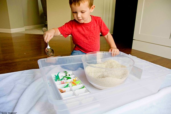 Un niño pequeño que realizaba una actividad sensorial en el compartimiento rescatando dinosaurios de una trampa de arroz en una actividad rápida y fácil de Busy Toddler