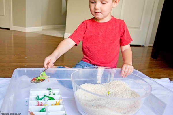 A toddler doing a sensory bin activity rescuring dinosaurs from a rice trap in a quick and easy activity from Busy Toddler