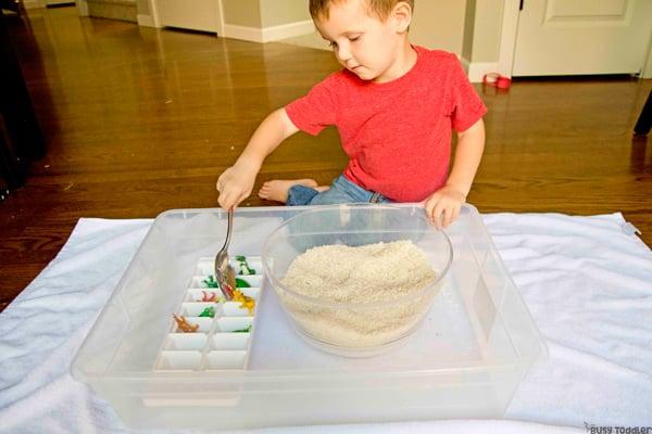 Un niño pequeño que realiza una actividad sensorial de compartimiento rescatando dinosaurios de una trampa de arroz en una actividad rápida y fácil de Busy Toddler