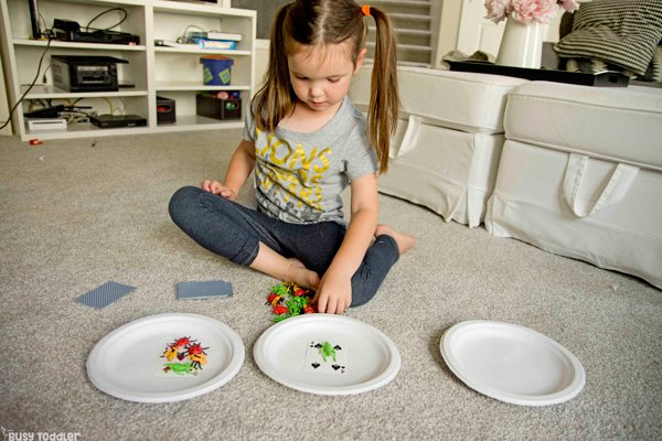 Preschooler learning about the concept of addition with a hands-on math activity on joining two groups of objects; preschooler is using counters and playing cards to show the addition / joing (activity by Busy Toddler)