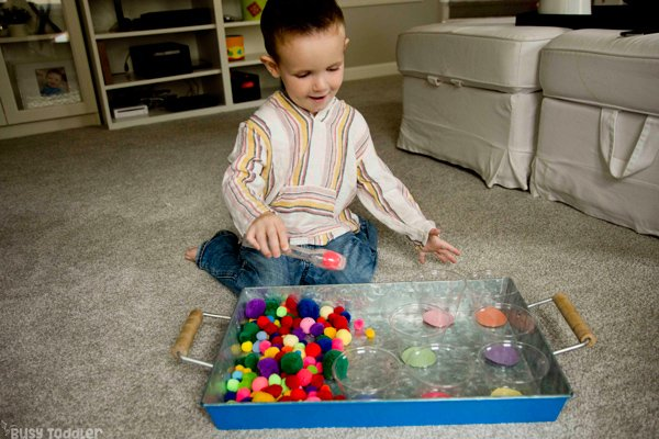 A toddler doing a pom pom color sorting activity using tongs and pom pom balls by Busy Toddler
