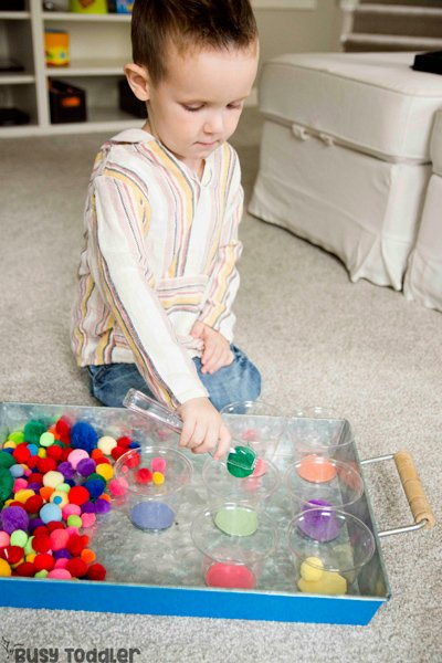 Un niño pequeño que realiza una actividad de clasificación de colores de pompones usando pinzas y bolas de pompones de Busy Toddler