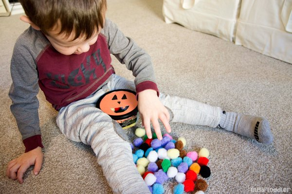 Toddler working on a fine motor skills pumpkin activity sticking pom pom balls into a recycled container in a quick and easy activity from Busy Toddler