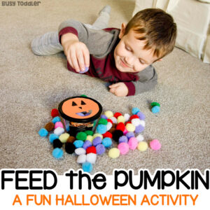 "Toddler working on a fine motor skills pumpkin activity called ""Feed the Pumpkin"" sticking pom pom balls into a recycled container in a quick and easy activity from Busy Toddler"