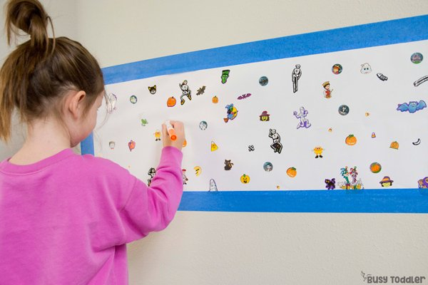 Preschooler playing a Halloween activity using stickers in a giant I-Spy format from Busy Toddler