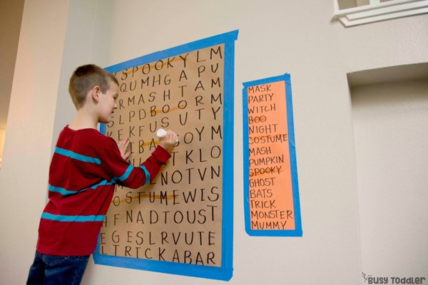 Big kid working on a giant word search activity for Halloween