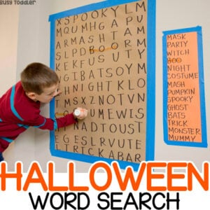 Kindergartener playing with a giant Halloween word search activity from Busy Toddler in a larger than life Halloween activity