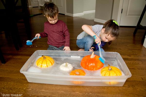 LAVADO DE CALABAZAS: un niño pequeño y un niño en edad preescolar jugando con una actividad sensorial de caída simple y lavando sus calabazas en una actividad rápida y fácil de Busy Toddler