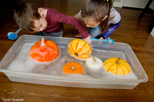 PUMPKIN WASH: A toddler and a preschooler playing with a simple fall sensory activity and washing their pumpkins in a quick and easy activity from Busy Toddler