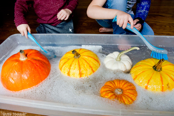 LAVADO DE CALABAZAS: un niño pequeño y un niño en edad preescolar jugando con una simple actividad sensorial de otoño y lavando sus calabazas en una actividad rápida y fácil de Busy Toddler
