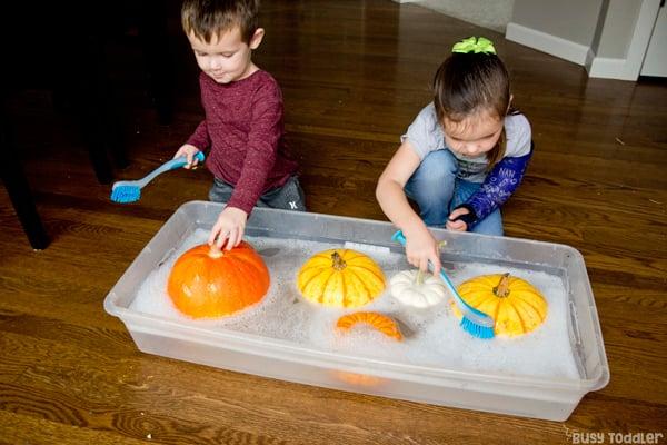 LAVADO DE CALABAZAS: un niño pequeño y un niño en edad preescolar que juegan con una actividad sensorial de caída simple y lavan sus calabazas en una actividad rápida y fácil de Busy Toddler