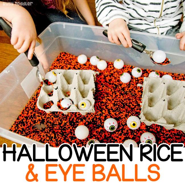 Un niño pequeño y un niño en edad preescolar jugando con un contenedor de arroz de Halloween en una actividad sensorial rápida y fácil de Busy Toddler