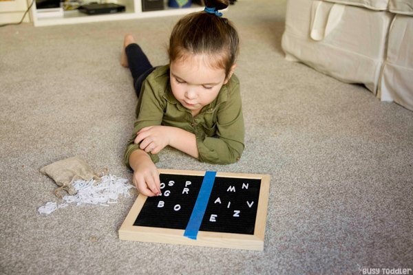 Preschooler playing with a letter board in a fun alphabet activity from Busy Toddler
