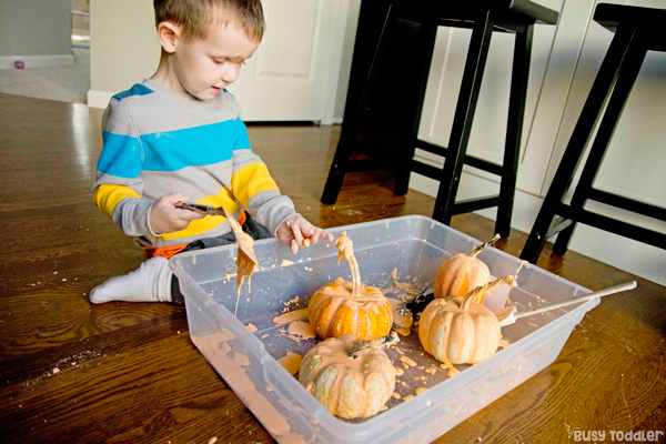 Toddler playing with a fun fall Oobleck activity - sensory play with pumpkins from Busy Toddler